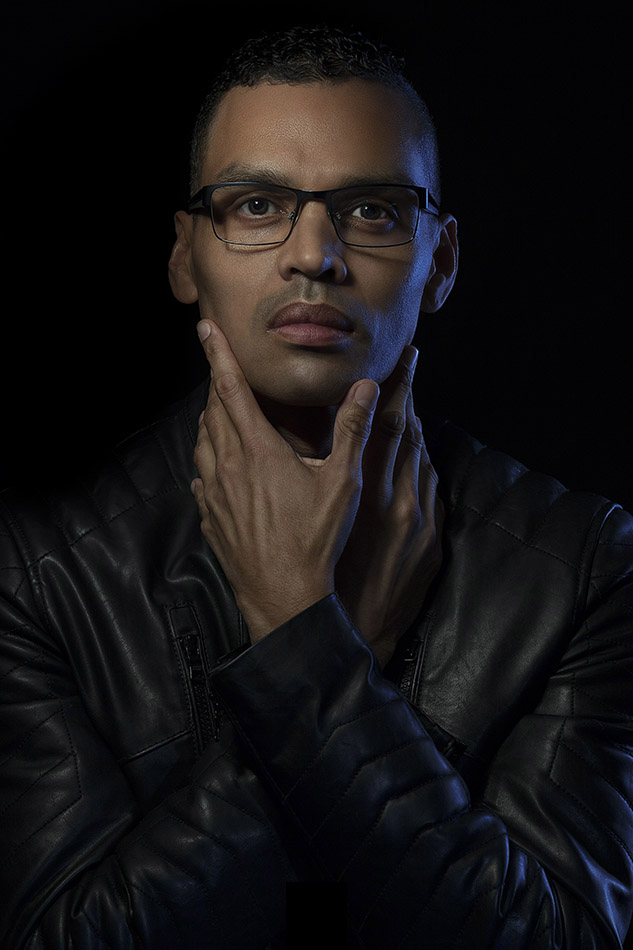 Low Key Dark Portrait Of A Black Man Wearing Glasses And Leather Jacket