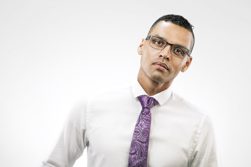 high key portrait of a black man wearing white shirt, glasses and purple tie