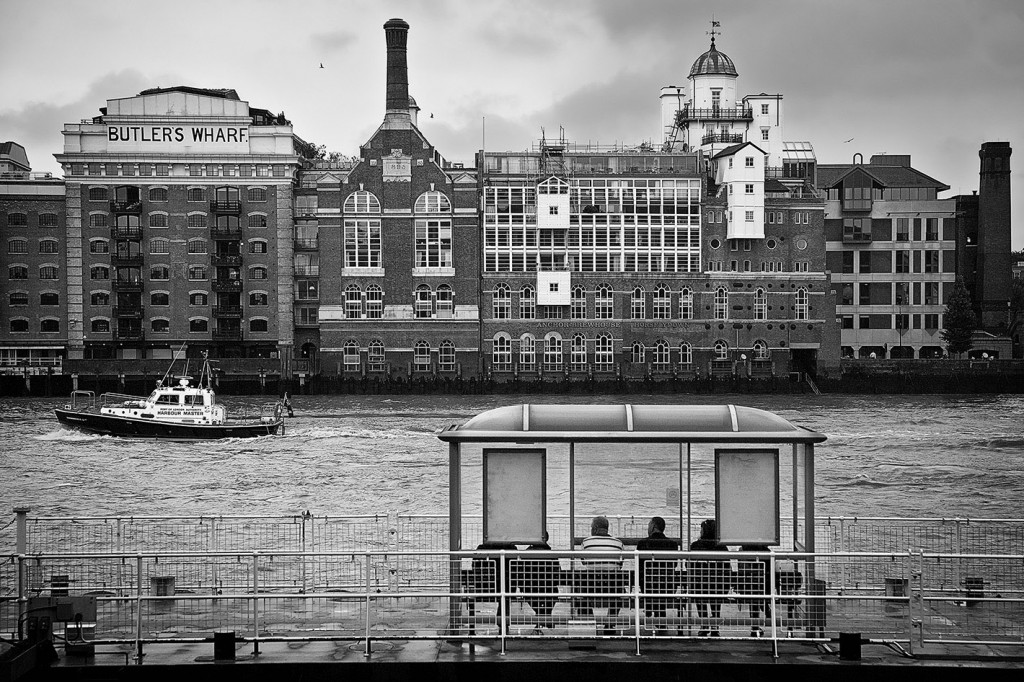 Black and white scene of river Thames and people seating at river bus stop, near Tower Bridge, looking at passing boat. With old brick warehouse building on the background.