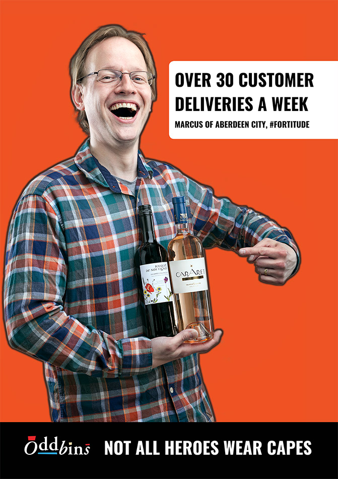 man with glasses holding two bottles of wine for an advertising campaign for OddBins