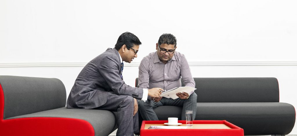 Accountant and his client sitting on a red and gray sofa discussing accounting matters and looking at a paper work