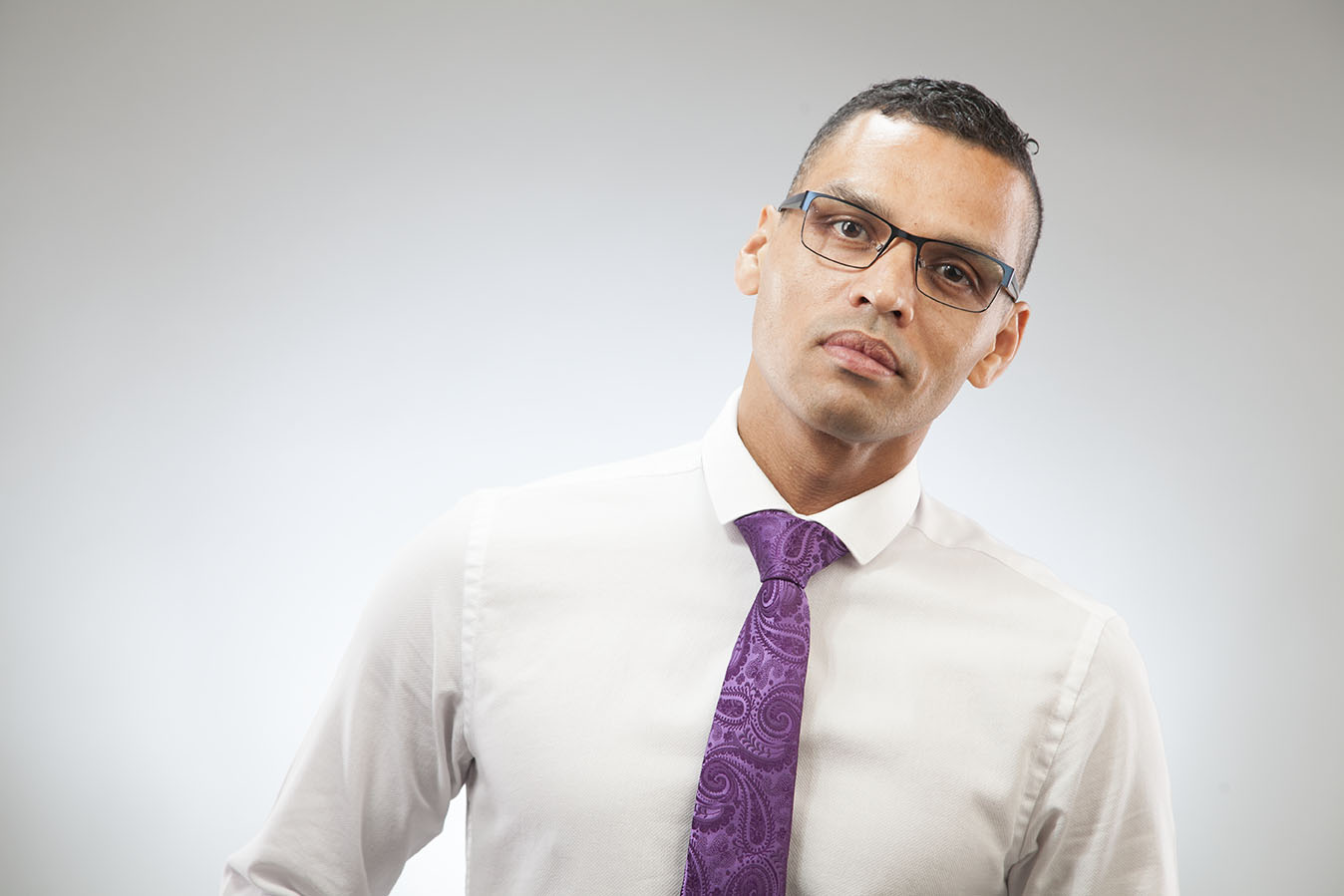 high key portrait of a black man wearing white shirt, glasses and purple tie before retouched