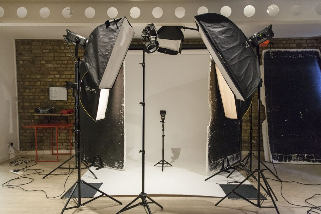 Photographic studio setup for portrait session, the image features bowens strobes white backdrop and light modifiers