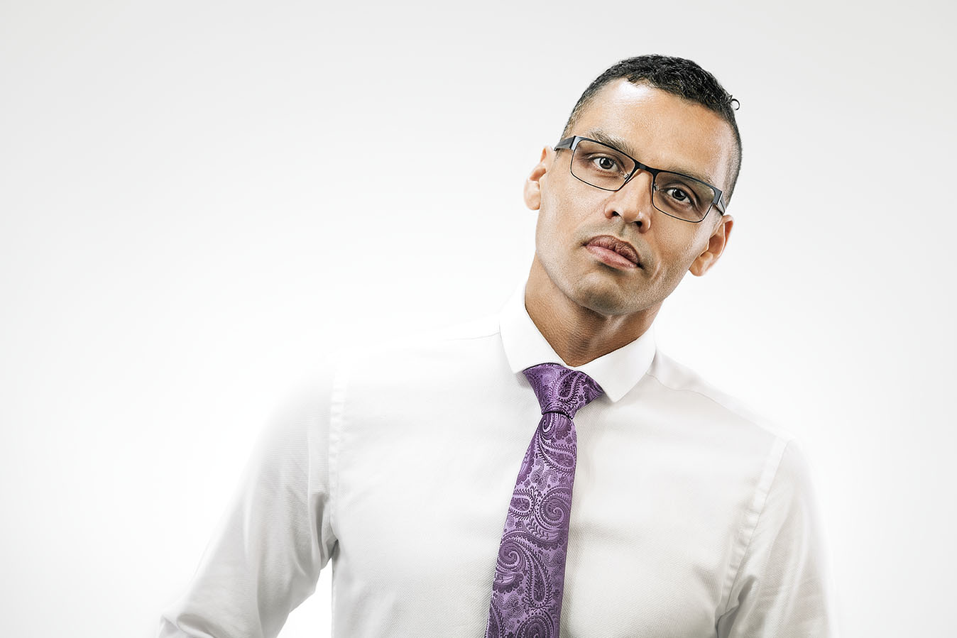 high key portrait of a black man wearing white shirt, glasses and purple tie after retouched