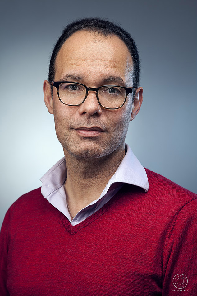 a portrait of a corporate sector man wearing glasses, red v neck sweater and a shirt. Photographed in a blue backdrop.