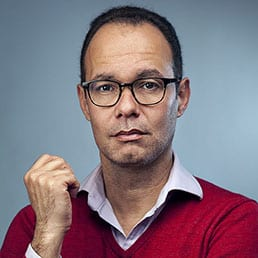 Corporate headshot portrait session of a man wearing glasses and red top, photographed in a studio with blue backdrop