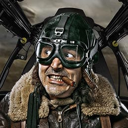 Creative portrait composite representing WWII pilot in the cockpit of hi aircraft engaged in an aerial battle, with the enemy aircraft on the background