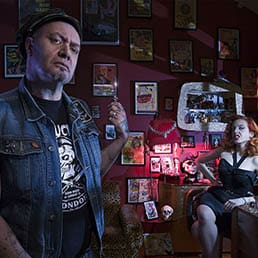 Tattooed rockabilly, demon, barber Mr. Ducktail is taking part in a creative photo shoot by holding razor blade in his dark and demonic barber shop with pinup model as his evil assistant on the background next to bottle of Jack Daniels.