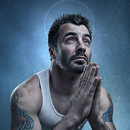 Creative headshots portrait photography session with a man covered in religious tattoos and praying pose.