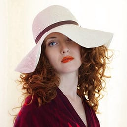 A fashion photography session featuring beautiful Italian female model with blue eyes and red hair - wearing red dress and white hat