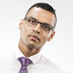 a mix race male model wearing glasses and white shirt with purple tie, photographed on a white studio background