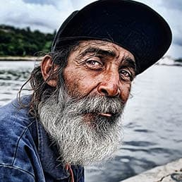 Portrait of Fisherman seating down near the port of Havana, Cuba - features a man, in his mid 50's, with white long beard