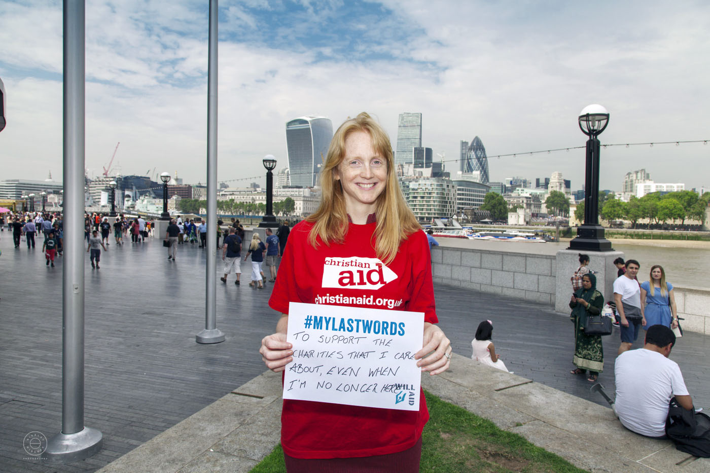 Young lady representing UK charity Will Aid is holding a sign with message #mylastwords on the background of city of London.
