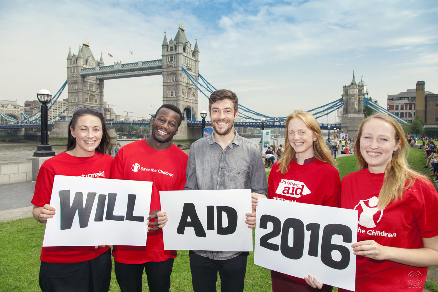 A group of staff holding signs saying Will Aid 2016 in front of Tower Bridge - London.